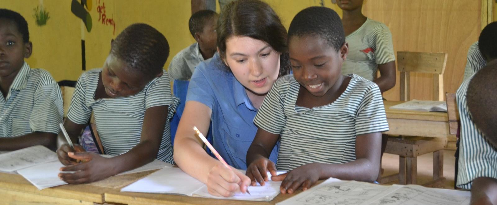 Maestra voluntaria ayuda a un estudiante en nuestro voluntariado para enseñar inglés en Ghana.